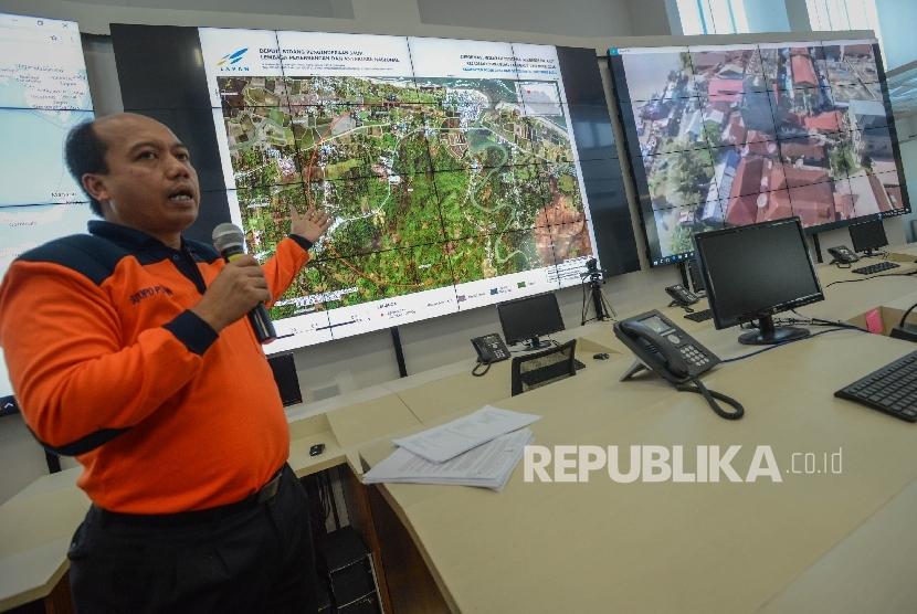 Kepala Pusat Data, Informasi, dan Humas Badan Penanggulangan Bencana (BNPB) Sutopo Purwo Nugroho lokasi bencana gempa di Provinci Aceh melalui layar di ruang pemantauan bencana Gedung BNPB, Jakarta, Jumat (9/12).