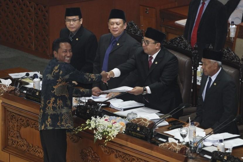 Ketua Badan Legislasi (Baleg) DPR Supratman Andi Agtas (kiri) menyerahkan berkas pembahasan revisi UU MD3 kepada Wakil Ketua DPR Fadli Zon pada Rapat Paripurna DPR di Kompleks Parlemen, Senayan, Jakarta, Senin (12/2).