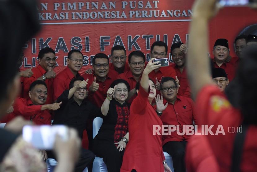 Ketua Bidang Politik dan Keamanan DPP PDI Perjuangan nonaktif Puan Maharani (ketiga kanan) berswafoto bersama Ketua Umum PDI Perjuangan Megawati Soekarnoputri (ketiga kiri), Sekjen PDIP Hasto Kristiyanto (kedua kanan), dan jajaran pengurus partai usai verifikasi faktual partai politik peserta Pemilu 2019 oleh KPU RI di kantor DPP PDI Perjuangan, Lenteng Agung, Jakarta, Senin (29/1).
