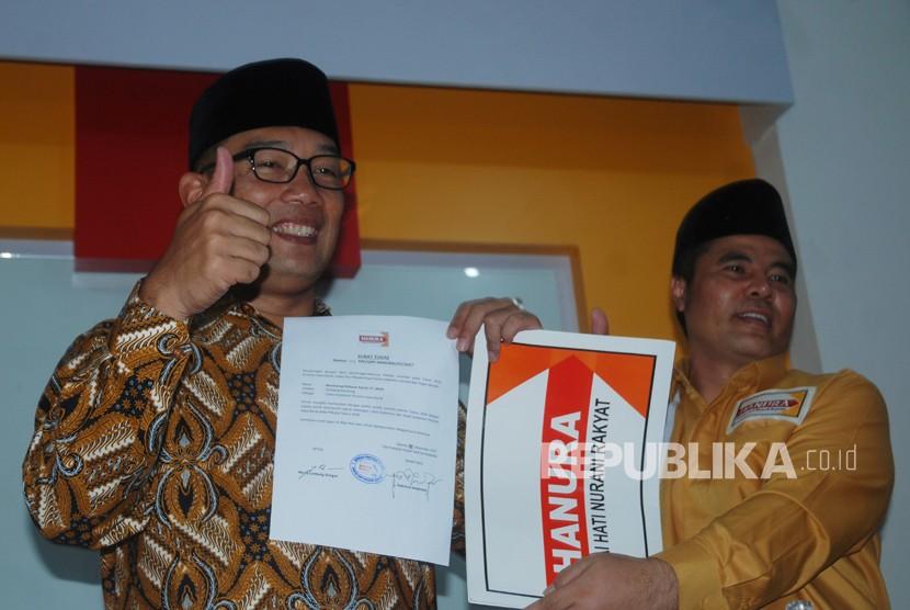 Ketua DPD Partai Hanura Jabar Aceng H.M Fikri (kanan) menyerahkan surat tugas pencalonan Pilgub Jabar kepada bakal calon Gubernur Jabar Ridwan Kamil (kiri), di Bandung, Jawa Barat, Senin (2/1).