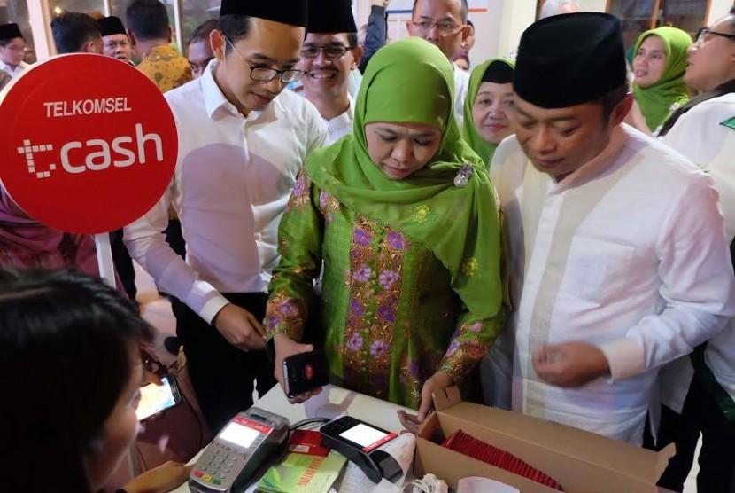Ketua Muslimat NU Khofifah Indar Parawansa didampingi Direktur Utama Telkomsel Ririek Adriansyah mencoba layanan Tcash