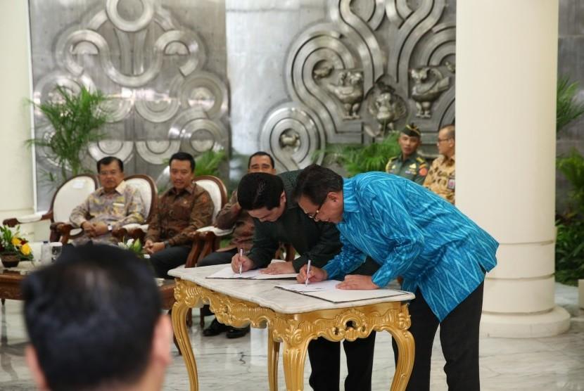 Ketua Pelaksana INASGOC Erick Thohir (kedua kanan) dan Managing Director Sinar Mas G. Sulistiyanto (kanan) bertukar naskah perjanjian kerjasama sponsorship Asian Games 2018 disaksikan Wakil Presiden Jusuf Kalla (kiri), Menpora Imam Nahrawi (kedua kiri) dan Ketua KONI Tono Suratman (ketiga kiri) di Jakarta, Rabu (6/12).