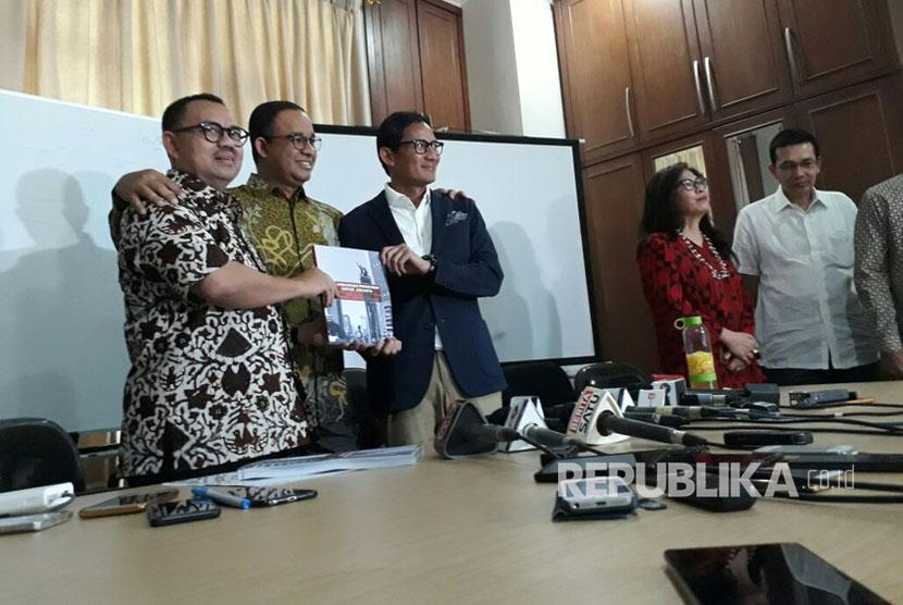 Ketua Tim Sinkronisasi Anies-Sandi, Sudirman Said (kiri) menyerahkan hasil kerja tim sinkronisasi pada pasangan Gubernur-Wakil Gubernur DKI Jakarta terpilih Anies Baswedan (tengah) dan Sandiaga Uno di Jakarta, Jumat (13/10).