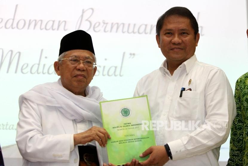 Ketua Umum Majelis Ulama Indonesia (MUI) Ma'ruf Amin (kiri) memberikan draft fatwa MUI kepada Menteri Kominfo Rudiantara ( kanan)pada acara Diskusi Publik dan Launching Fatwa MUI tentang Hukum dan Pedoman Bermuamalah Melalui Medsos di Kementerian Kominfo, Jakarta, Senin (5/6).