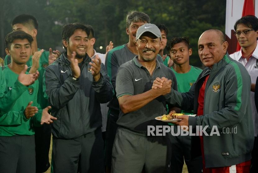 Ketum PSSI Edy Rahmayadi bersalaman dengan pelatih timnas U-16 Fakhri Husaini pada acara pelepasan timnas Indonesia U-16 di Stadion Atang Sutresna, Kompleks Kopassus, Jakarta, Rabu (13/9).