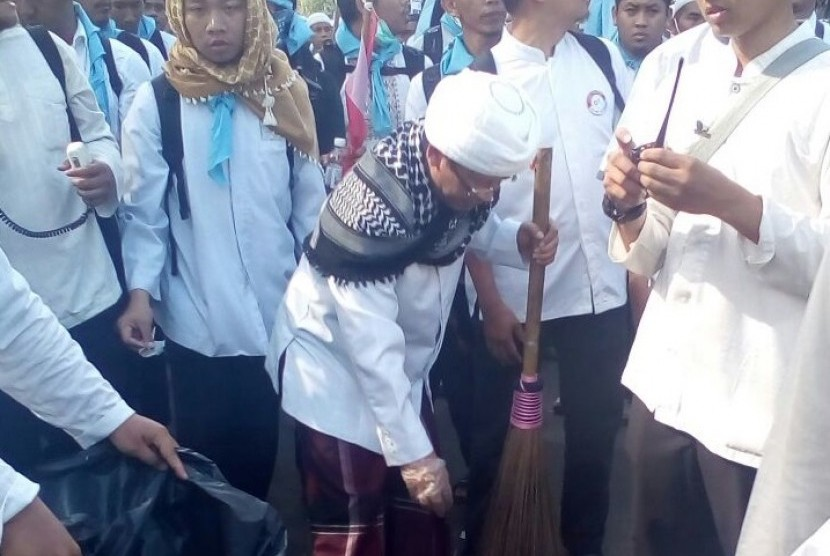 KH Abdullah Gymnastiar atau Aa Gym memunguti sampah-sampah massa aksi damai 'Bela Islam Jilid II'.
