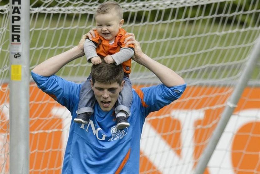 Striker timnas Belanda, Klaas-Jan Huntelaar, menggendong anak lelakinya, Seb, usai menggelar sesi pertama latihan timnas di Lausanne, Swiss, Jumat (18/5).