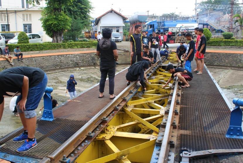 Komunitas pecinta kereta mencuci turntable kereta yang umurnya sudah 100 tahun di Dipo Jatinegara, Ahad (29/5).