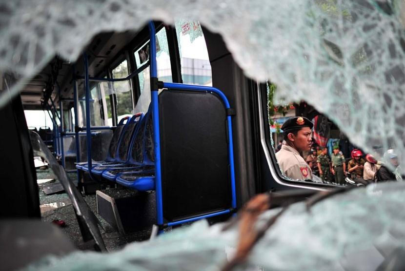 Polisi menjaga Bus Transjakarta yang dirusak massa di Jl Mampang Prapatan, Jakarta Selatan, Jumat (13/7).  (Yogi Ardhi/Republika)