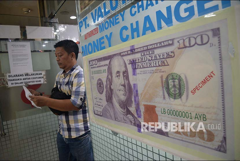 Konsumen menukarkan mata uang asing di jasa penukaran uang asing Valuta Artha Mas ITC Kuningan, Jakarta,Kamis (26/4). Nilai tukar rupiah rebound pada perdagangan Kamis (26/4), Rupiah di tutup menguat 0,22% ke posisi Rp 13.891 per dolar AS, setelah dibuka di level Rp 13.919 per dolar AS.
