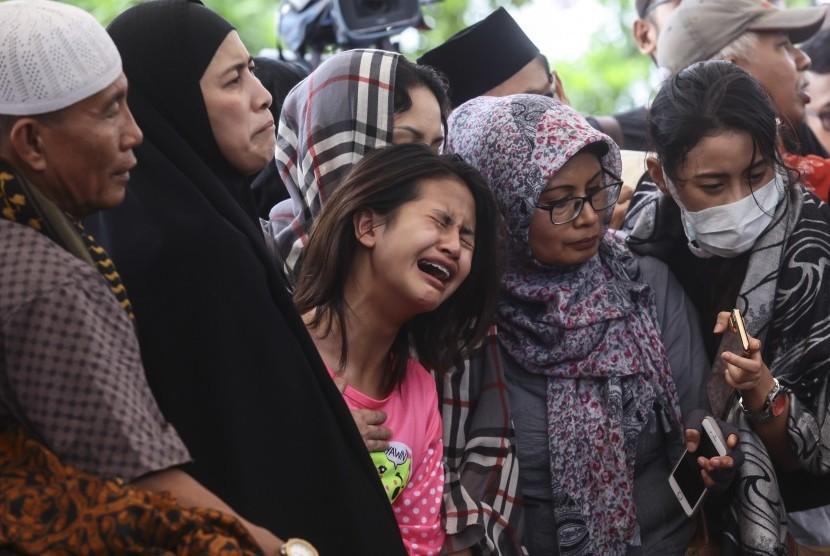 Korban selamat dalam kasus pembunuhan Pulomas Zanette Kalila (tengah) bersama Ibunya Rosi Herawati (kedua kiri) menghadiri pemakaman keluarga mereka yang tewas dalam kasus itu di TPU Tanah Kusir, Jakarta, Rabu (28/12).