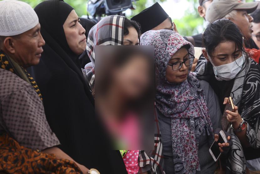Korban selamat dalam kasus pembunuhan Pulomas Zanette Kalila (tengah) bersama Ibunya Almyanda Safira (kedua kiri) menghadiri pemakaman keluarga mereka yang tewas dalam kasus itu di TPU Tanah Kusir, Jakarta, Rabu (28/12).