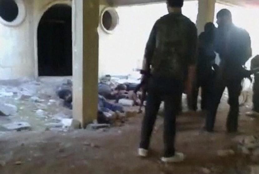 Kubu oposisi mengelilingi tentara pemerintah Suriah yang sudah tewas setelah penembakan. Rekaman video ini beredar di laman media sosial pada Kamis lalu (1/11).