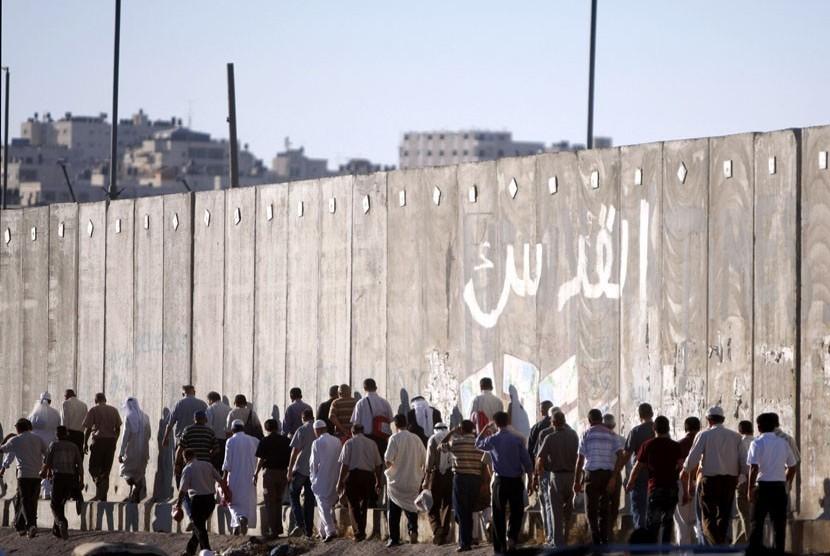 Laki-laki Palestina melintas disamping tembok pemisah Israel dalam perjalanan mereka untuk shalat Jumat di Masjid Al Aqsa di Yerusalem, Jumat (10/8). (Majdi Muhammad/AP)