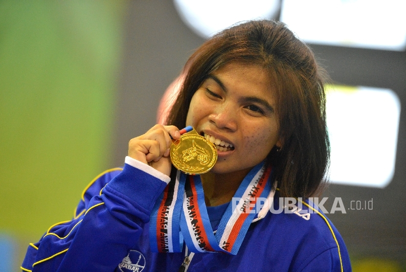 Lifter putri Jabar, Sri Wahyuni Agustani menggigit medali usai bertanding pada kelas 48 kg di GOR Sabilulungan Jalak Haruat,Kabupaten Bandung, Jabar,Selasa (20/9). Sri juga adalah peraih perak Olimpiade Rio 2016.
