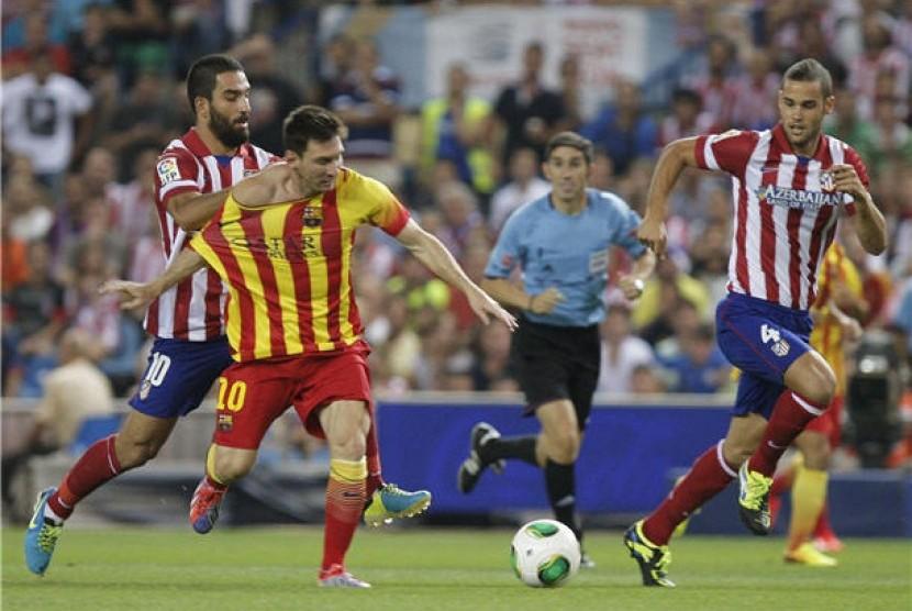 Lionel Messi (tengah), striker andalan Barcelona, menggiring bola saat menghadapi Atletico Madrid di leg pertama Piala Super Spanyol di Vicente Calderon, Madrid, Rabu (21/8).