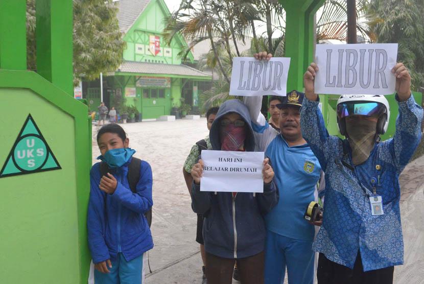 Guru dan pelajar memegang pegumuman libur sekolah ketika hujan abu vulkanik di sekolahmereka di Kota Madiun, Jatim, Jumat (14/2). (Antara/Fikri Yusuf)
