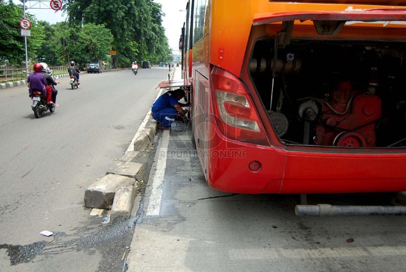 Seorang petugas memperbaiki bus TransJakarta yang mogok di Jalan Gunung Sahari Raya, Jakarta Pusat, Selasa (25/2). (foto: Raisan Al Farisi)