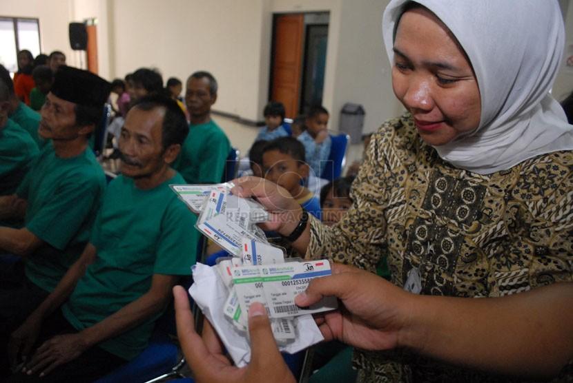 Petugas membagikan kartu BPJS kesehatan kepada warga   di Panti Sosial Bina Insan Bangun Daya 2, Cipayung, Jakarta Timur, Kamis (24/4). (Republika/Rakhmawaty La'lang)