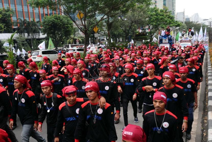 Massa buruh Konfederasi Serikat Pekerja Indonesia (KSPI) se-Jabodetabek melakukan aksi longmarch saat demo di Kantor Kemenkumham, Jakarta, Kamis (19/6).  (Republika/Tahta Aidilla)