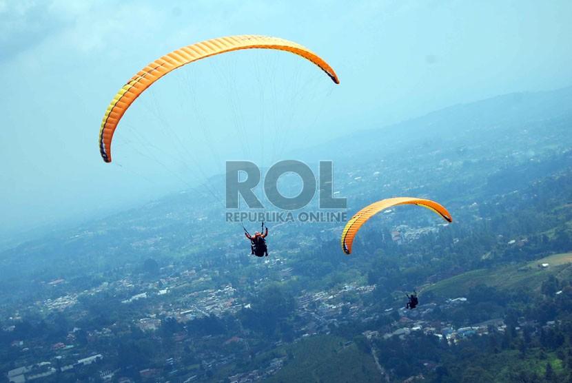Pengunjung bersama pemandu wisata aero sport menerbangkan paralayang yang berada di kawasan Puncak Pass, Bogor, Sabtu (2/8). (Republika/Raisan Al Farisi)