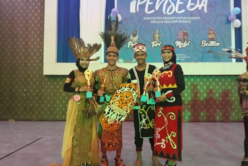 Mahasiswa AMIK BSI Pontianak, Satriansyah (kedua dari kiri) dan Fitri Febriyani (kiri) menjadi juara pertama lomba pakaian adat tingkat Provinsi Kalimantan Barat.