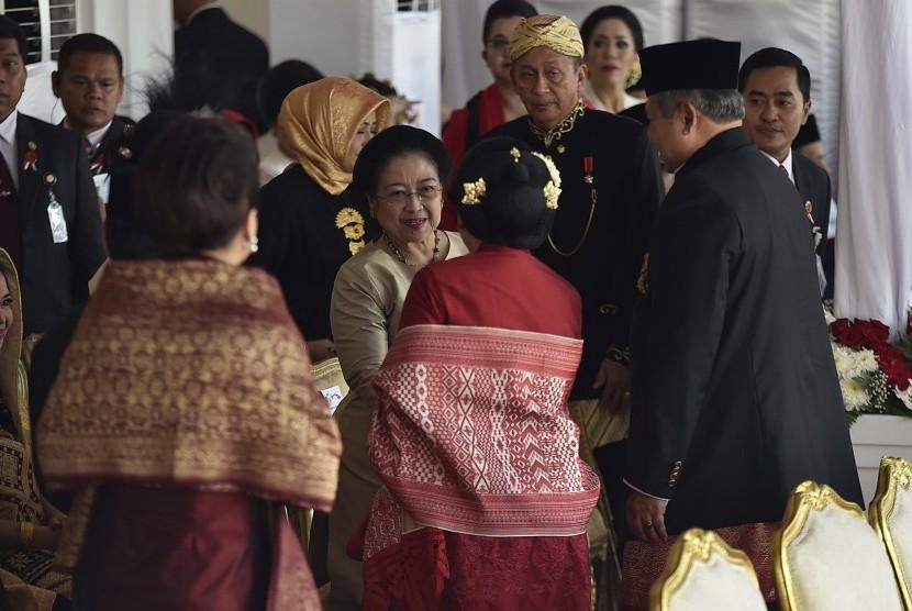 Mantan Presiden Megawati Soekarnoputri (tengah) berjabat tangan dengan mantan Presiden Susilo Bambang Yudhoyono (kanan) beserta istri Ani Yudhoyono (kedua kanan) saat menghadiri upacara peringatan detik-detik proklamasi kemerdekaan RI di Istana Merdeka, Jakarta, Kamis (17/8).
