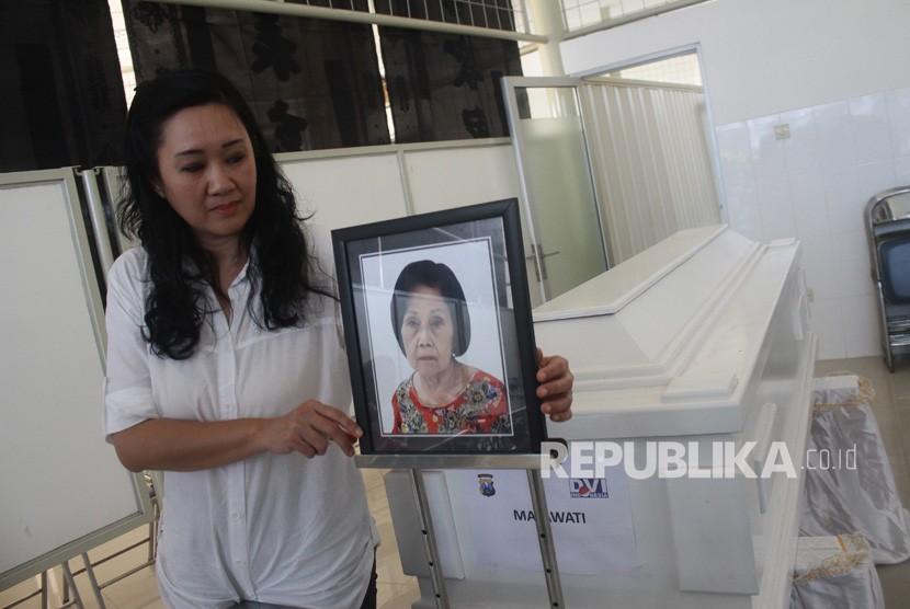 Maria Hamdani, memasang foto bibinya, Mayawati yang menjadi korban bom gereja Surabaya di Rumah Persemayaman Gotong Royong, Malang, Jawa Timur, Senin (14/5).