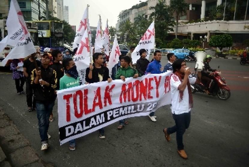 Masa yang tergabung dalam Kaukus Muda Indonesia (KMI) menggelar aksi unjuk rasa menentang politik uang di Bundaran HI, Jakarta, Jumat (4/4).