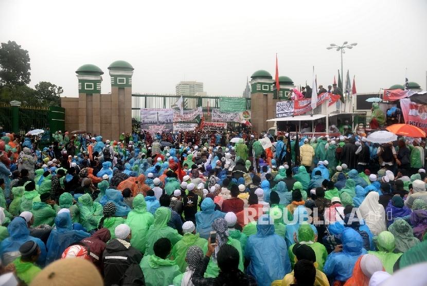 Massa Aksi 212 memadati pintu gerbang DPR RI dalam guyuran hujan, Jakarta, Selasa (21/2).