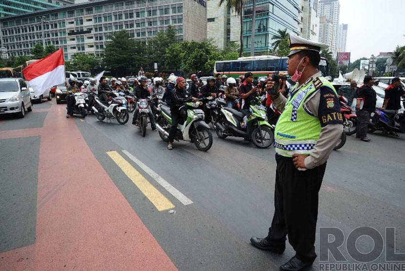 Massa Front Transportasi Jakarta menggelar aksi menolak perda pembatasan sepeda motor di kawasan Bundaran HI, Jakarta, Senin (22/12). (Republika/Tahta Aidilla)