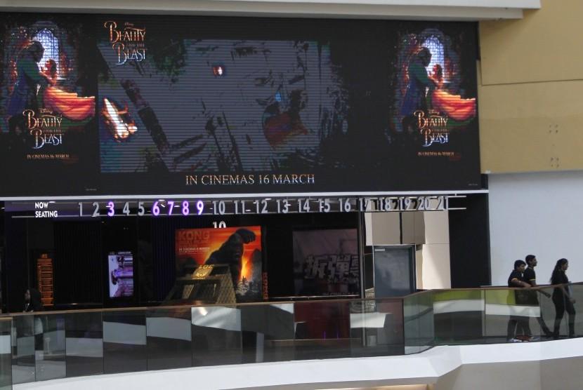 Masyarakat berjalan di bawah layar besar yang menunjukkan iklan film Beauty and the Beast di Kuala Lumpur, Malaysia.