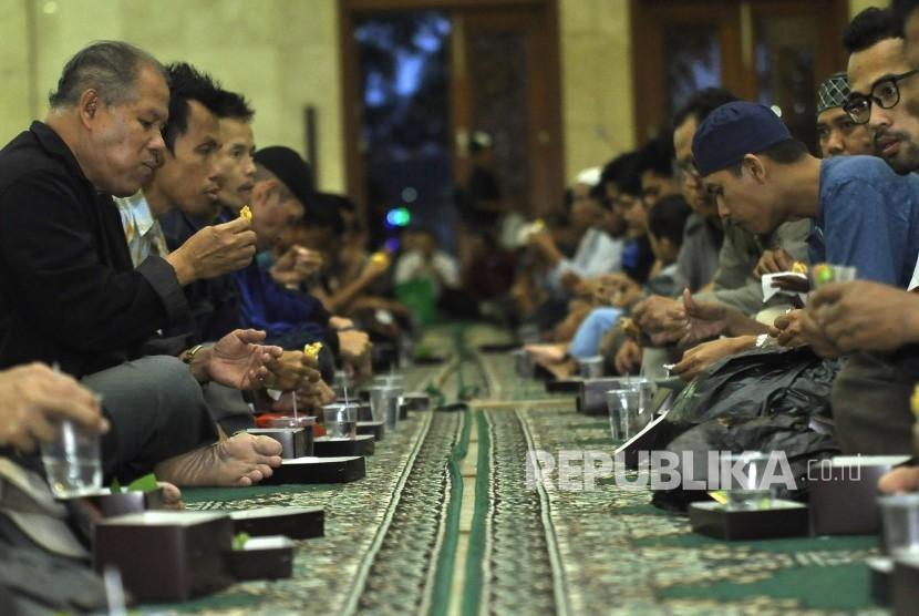 Masyarakat menyantap takjil saat berbuka puasa di Masjid Raya Agung Jawa Barat, Alun-alun Kota Bandung, Senin (29/5).