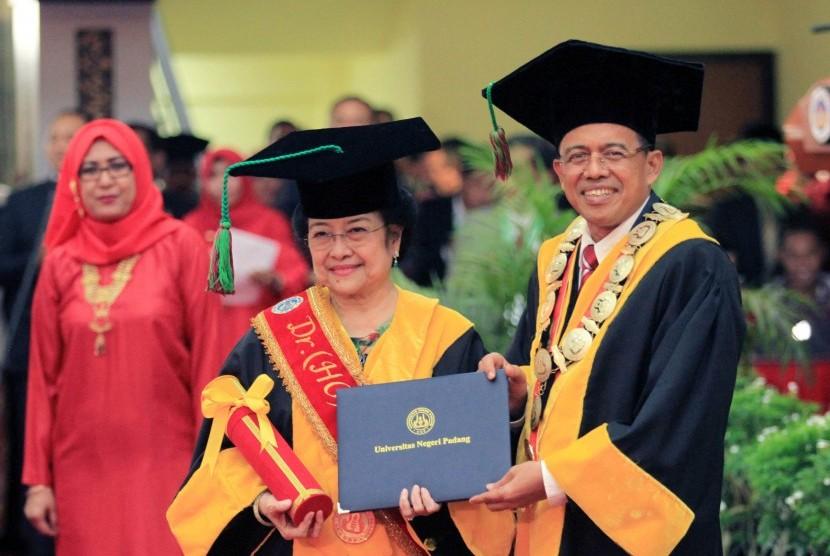 Megawati Soekarnoputri (tengah) menerima piagam Doktor yang diberikan Rektor Universitas Negeri Padang Ganefri (kanan) saat penganugerahan gelar Doktor Honoriis Causa Bidang Politik Pendidikan, di auditorium Universitas Negeri Padang (UNP), Sumatera Barat, Rabu (27/9).