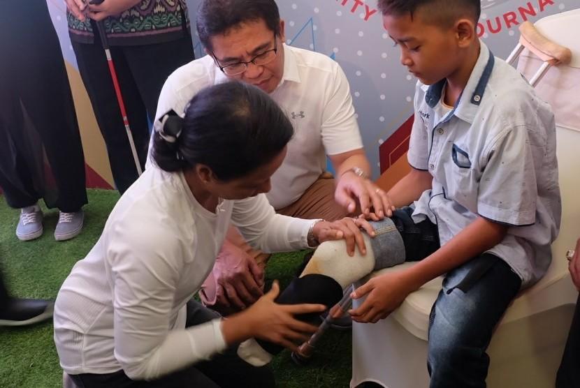 Menteri BUMN RI Rini M. Soemarno didampingi Direktur Utama Telkom Alex J. Sinaga saat memasangkan kaki palsu kepada penyandang disabilitas pada acara Telkom Disability Care  - Charity Golf Tournament di Jakarta (5/8).
