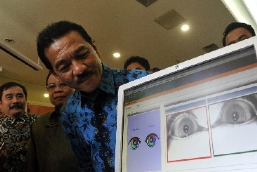 Menteri Dalam Negeri Gamawan Fauzi mengecek data e-KTP miliknya dengan sistem pemindaian iris mata di Kementerian Dalam Negeri, Jakarta Pusat.