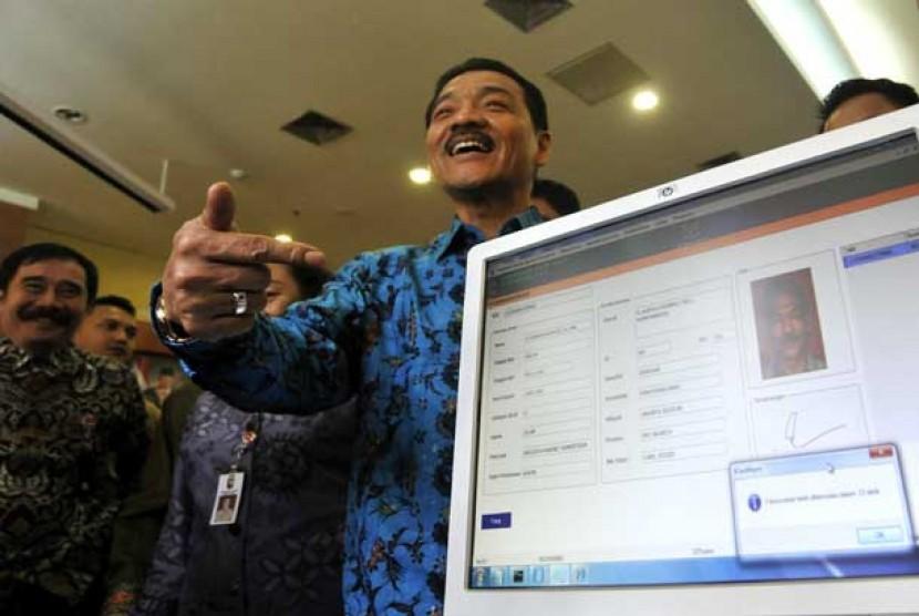 Menteri Dalam Negeri Gamawan Fauzi (tengah) tersenyum seusai memindai data e-KTP miliknya di Kementerian Dalam Negeri, Jakarta Pusat, Kamis (8/11).