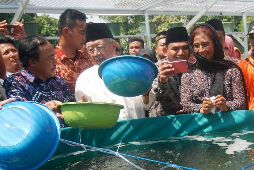 Menteri Kelautan dan Perikanan Susi Pudjiastuti (kanan) dan Pengasuh Ponpes Tebuireng KH Salahuddin Wahid (tengah) menebar benih ikan lele sistem bioflok di SMA Trensains Tebuireng di Desa Jombok, Ngoro, Jombang, Jawa Timur, Ahad (13/8).