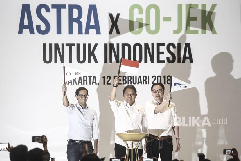 Menteri Komunikasi dan Informatika Rudiantara (tengah) mengangkat bendera bersama Presiden Direktur PT Astra International Tbk Prijono Sugiarto (kanan) dan CEO & CO-Founder GO-JEK Nadiem Makariem (kiri) seusai penandatanganan kerja sama Investasi antara Astra Internasional dengan GO-JEK di Jakarta, Senin (12/2).