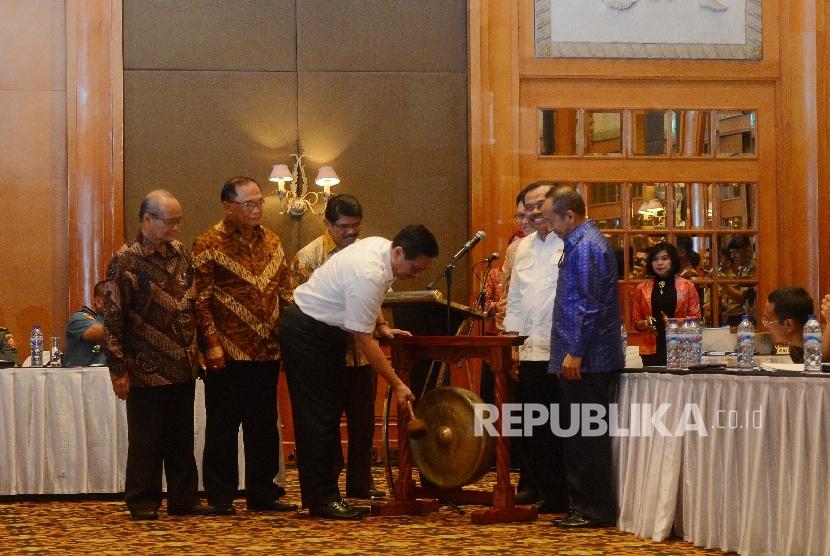 Menteri Koordinator Bidang Politik, Hukum, dan Keamanan Luhut Binsar Pandjaitan memukul gong sebagai tanda dibukanya Simposium Nasional yang bertema Membedah Tragedi 1965, Pendekatan Kesejarahan di Jakarta, Senin (18/4). (Republika / Raisan Al Farisi )