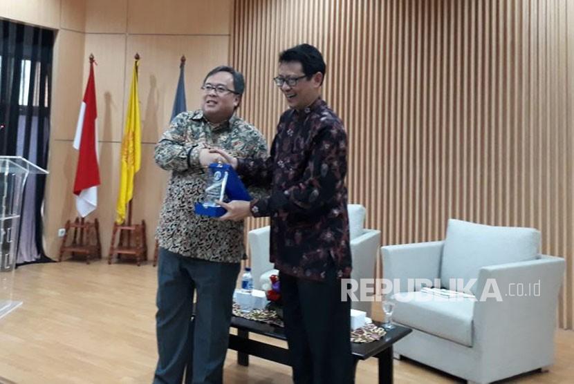 Menteri Perencanaan Pembangunan Nasional/Kepala Bappenas Bambang P. S Brodjonegoro menerima tanda apresiasi dari Kepala Pusat Kegiatan Mahasiswa FEB UIPribadi Setiyanto usai memberi paparan tentang ekonomi pembangunan Islam di Kampus FEB UI, Kamis (26/10).