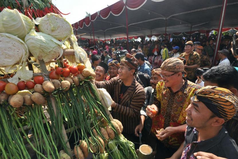 Menteri Pertanian Andi Amran Sulaiman (mengenakan surjan lurik) ikut berebut gunungan hasil pertanian saat menghadiri peribgatan Hari Tani tingkat Jawa Tengah, di halaman kantor Gubernuran, Semarang, Sabtu (23/9).