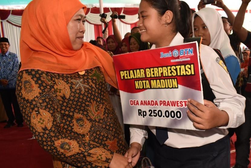 Menteri Sosial Khofifah Indar Parawansa (kiri) menyerahkan beasiswa kepada pelajar berprestasi saat penyaluran bantuan sosial nontunai Program Keluarga Harapan (PKH) di Alun-alun Kota Madiun, Jawa Timur, Senin (17/4).