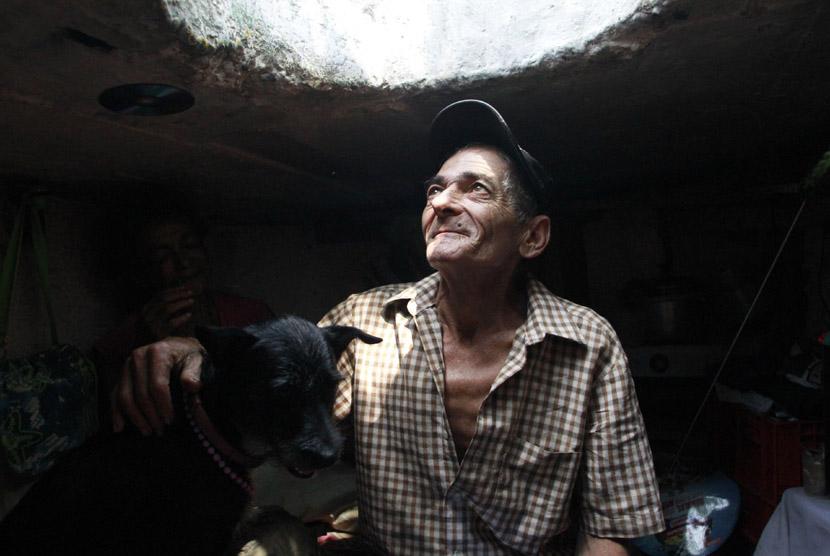 Miguel Restrepo bermain dengan anjingnya di rumah selokannya di kota Medelline,Kolombia, Selasa (4/12). (Reuters/Albeiro Lopera)