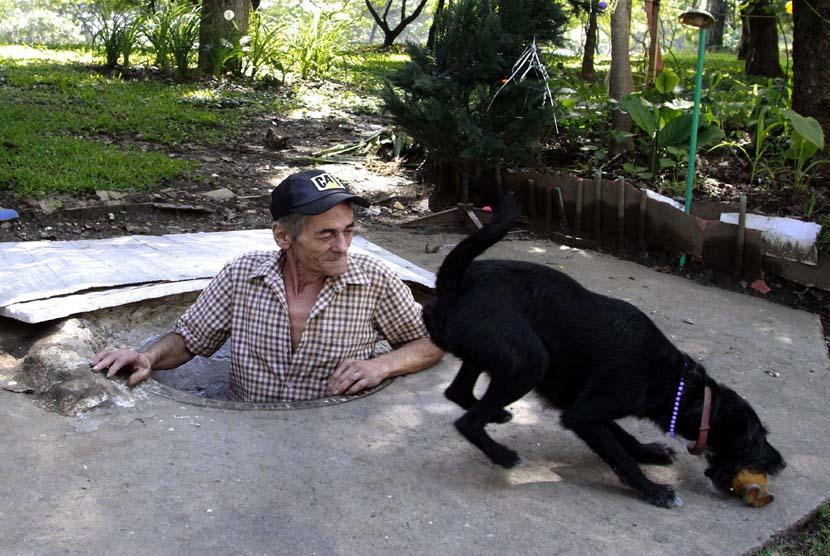 Miguel Restrepo bermain dengan Blackie anjingnya di rumah selokan di kota Medelline,Kolombia, Selasa (4/12).