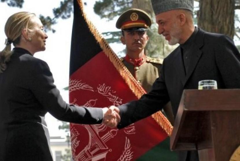 Mitra utama: Hillary Clinton berjabat tangan dengan presiden Afghanistan Hamid Karzai setelah konferensi pers.