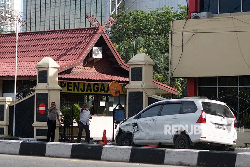 Mobil minibus yang digunakan pelaku teror dalam kondisi rusak di depan pintu masuk Polda Riau, di Pekanbaru, Riau, Rabu (16/5).