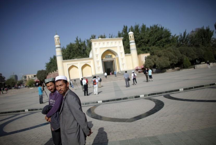 Muslim etnis Uighur berjalan di depan sebuah masjid di Kashgar, Xinjiang, Cina.