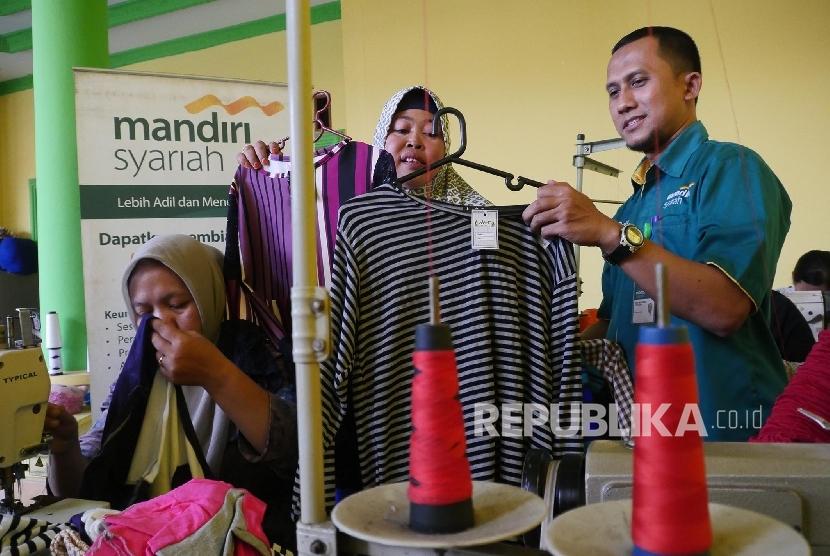 Nasabah Usaha Mikro Kecil dan Menengah (UMKM) Bank Mandiri Syariah Sumairah (kiri) memperlihatkan produknya kepada Pegawai Retail Sales Executive Mandiri Syariah saat meninjau workshopnya di Citeureup Bogor, Jawa Barat, Rabu (13/9).