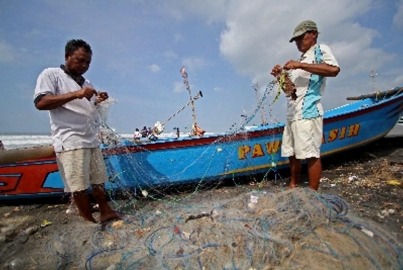 Nelayan tradisional membenahi jaring (ilustrasi).